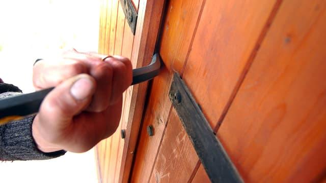 Eine Hand an einem Brecheisen, das eine Tür aubricht.