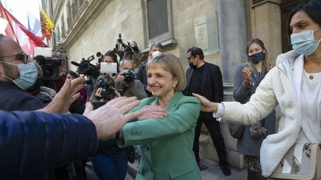 Frau mit grüner Jacke begrüsst jubelnde Anhänger. Medienleute mit Kamera filmen. Dahinter Genfer Fahne.