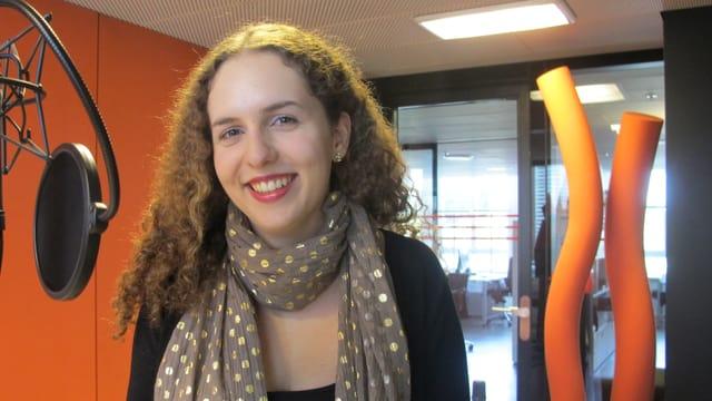 Eine junge Frau mit Schal und langen Haaren steht vor einem Mikrofon in einem Studio.