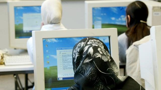 Frauen mit Kopftüchern von hinten, sitzen an Computern, daneben eine Frau ohne Kopftuch