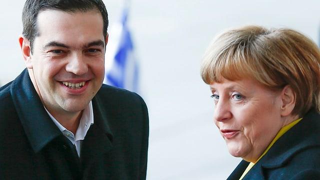 Tsipras uns Merkel bei Begrüssung in Berlin, in dunkeln Mänteln gekleidet.