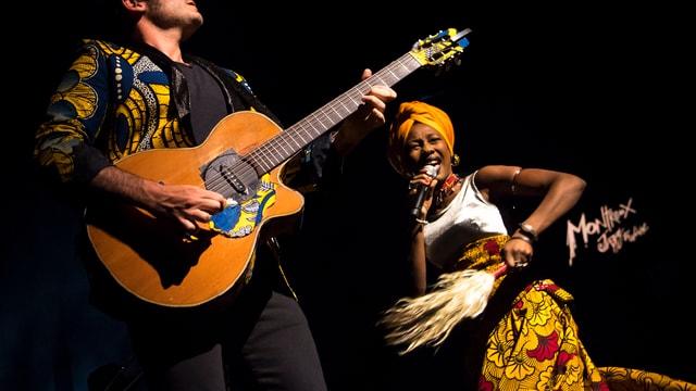 Ein Mann mit Gitarre und eine Frau in afrikanischer Tracht auf der Bühne.