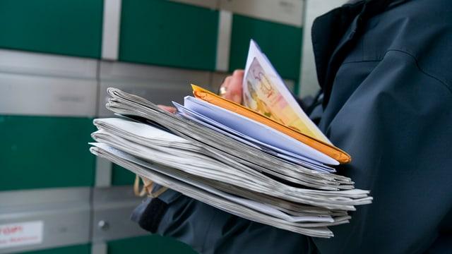 Ein Briefträger verteilt Post in einen Briefkasten bei einem Mehrfamilienhaus.