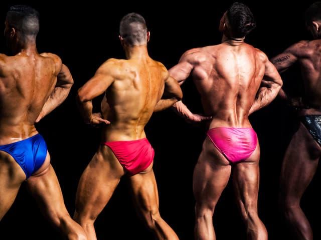 Vier Männer in knappen Badehosen präsentieren ihre Rückenmuskeln.