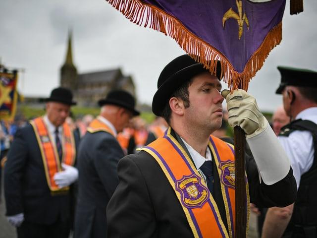 Im Vordergrund ein Umzugsteilnehmer mit einer Fahnenstange in der Hand. Daneben ein Polizist, im Hintergrund die Kirche von Drumcree.