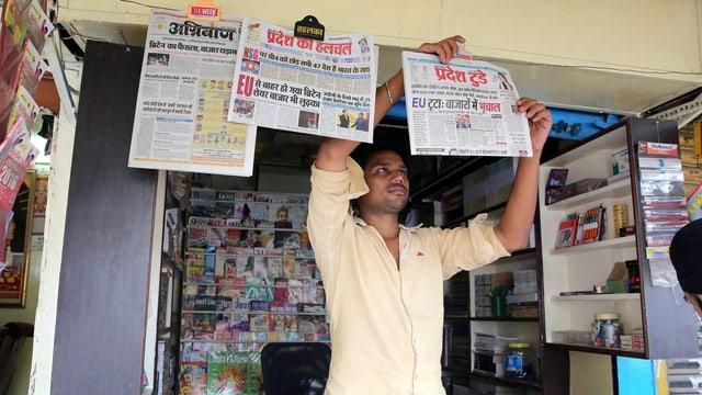 Ein Kioskverkäufer pinnt indische Zeitungen an eine Schnur.