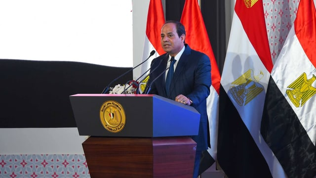Al-Sissi bei einer Rede an einem Pult vor einer Reihe von ägyptischen Fahnen.