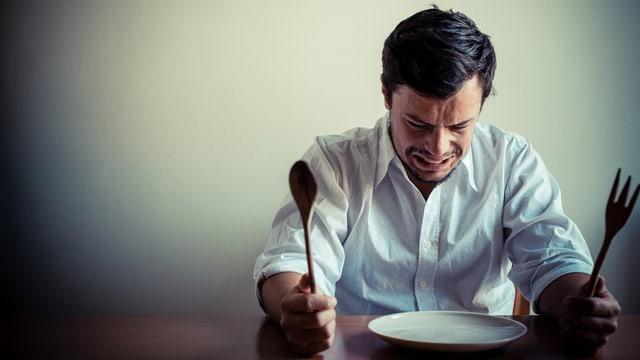 Mann sitzt mit Gabel und Messer und verzerrtem Gesicht vor einem leeren Teller.