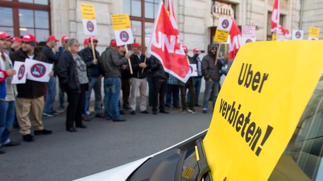 Protest gegen uberPOP. Menschen protestieren mit Schildern und Transparenten.