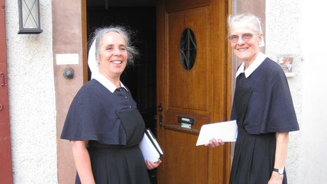 Zwei Diakonissen stehen vor einer hölzernen Haustüre.