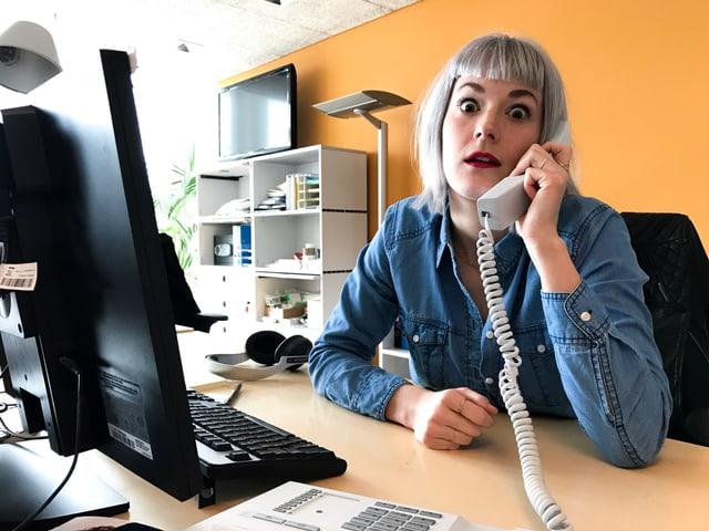 Tina Nägeli hat einen Telefonhörer in der Hand.