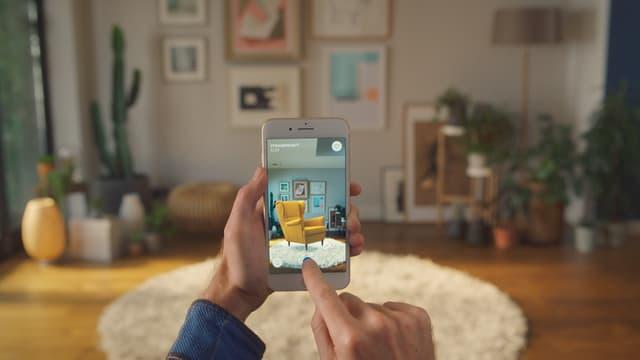 Eine Hand mit einem Smartphone, darin ein Stuhl, wie er in der echten Stube hintendran aussehen würde.