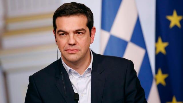 Tsipras vor einem Mikrofon, hinter ihm eine griechische und eine EU-Fahne.