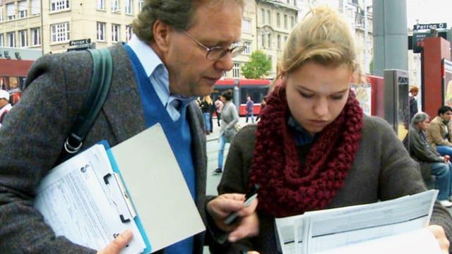 Ein Mann lässt ein Formular von einer Frau unterschreiben.