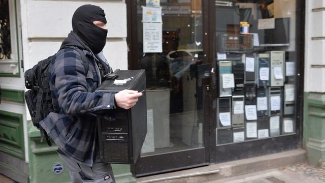 Ein vermummter Polizist trägt einen Desktop-PC aus dem Haus.