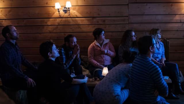 Eine Gruppe von Menschen sitz in einem abgedunkelten raum. Sie werden vom blauen Licht eines Fernsehbildschirmes beleuchtet.