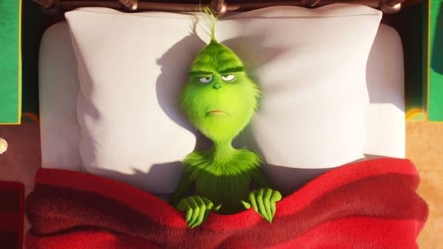 Blick von oben auf ein Bett. Darin liegt ein grimmig dreinschauendes, haariges Monster, die Decke hält es mit beiden Händen vor der Brust.