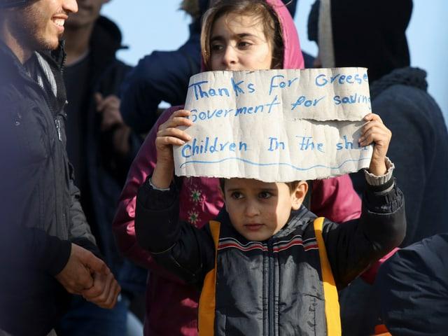 Kind hält Dankes-Plakat hoch