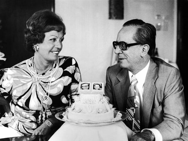 ein schwarz-weiss Foto eines Ehepaars vor seinem Hochzeitskuchen