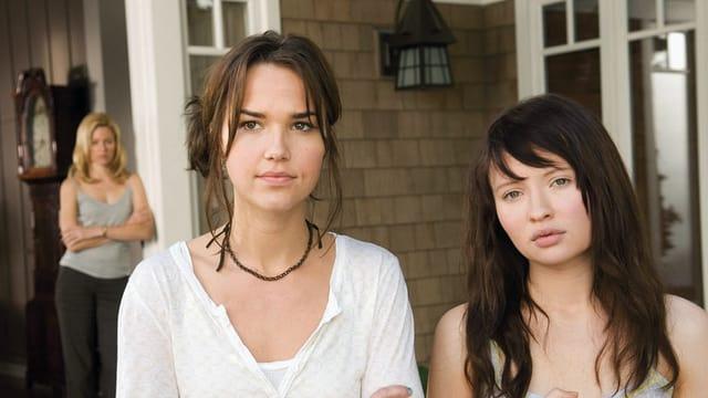 Zwei junge Frauen stehen im Vordergrund, dahinter ist eine Frau mittleren Alters zu sehen.