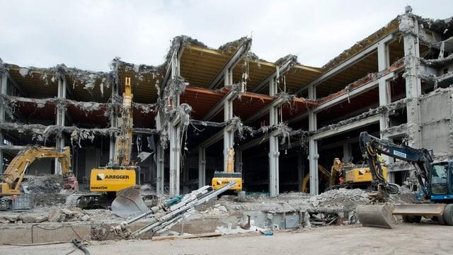 Abriss des Messegebäudes in Basel, Bagger bauen das Gebäude zurück.
