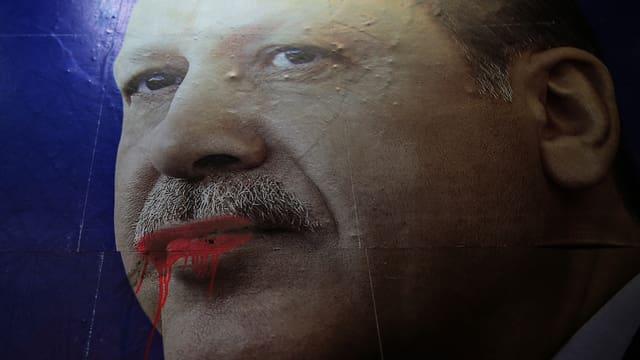 Wahlplakat mit Erdogans Konterfei, seine Lippen wurden mit roter Farbe beschmiert.