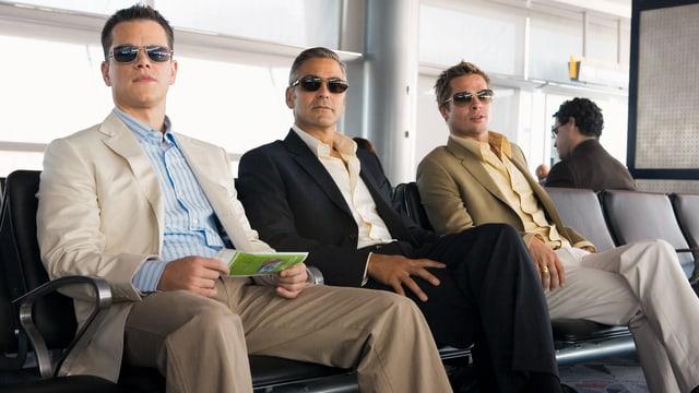 Dre Männer warten an einem Flughafen.