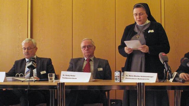 Zwei Ordensschwestern und zwei Experten sitzen an einem Tisch.