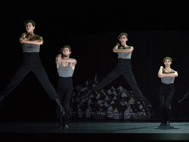 Tänzer springen in die Luft. Sie tragen schwarze Hosen und graue Trägershirts aus Wollstoffen.