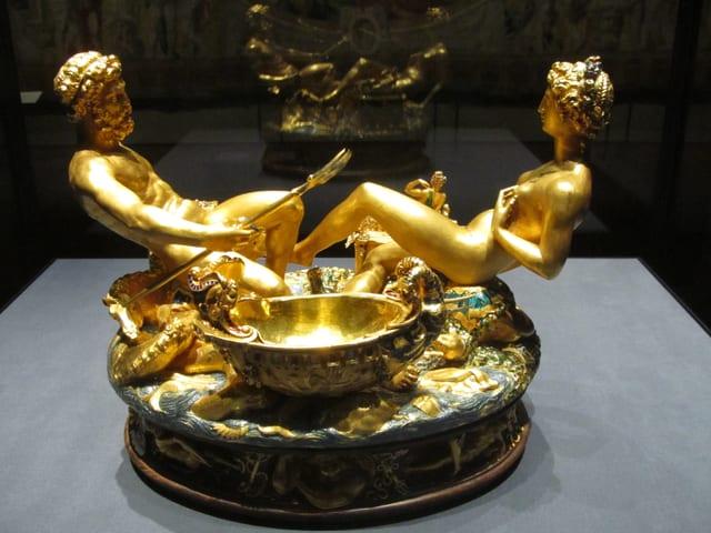 Skulptur aus Gold: Zwei halb liegend-halb sitzende Figuren, davor eine Schale.