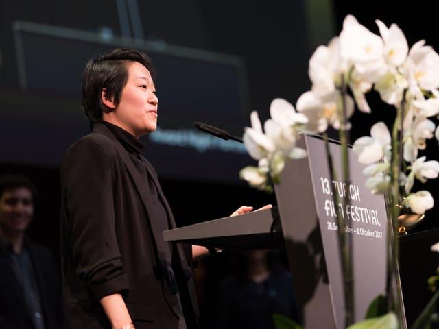 Regisseurin Kirsten Tan steht auf der Bühne.