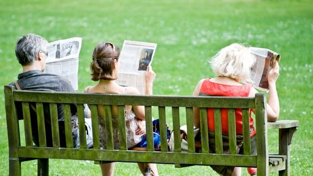 Drei Personen sitzen auf einer Parkbank und lesen Zeitung.