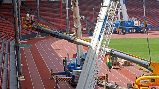 Mehrere Pneukräne stellen im Stadion Letzigrund vor der Tribüne Dachstützen auf.