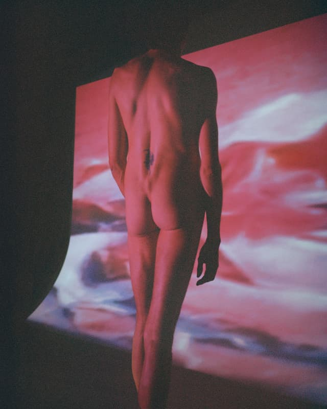 Ein nackter Mann von hinten, er steht vor einer Leinwand, der Körper ist rot beleuchtet.
