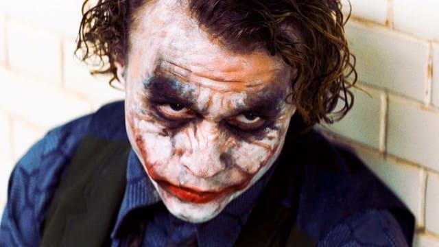 Filmszene: Mann mit weiss geschminktem Gesicht und ungleichmässig rot geschminktem Mund