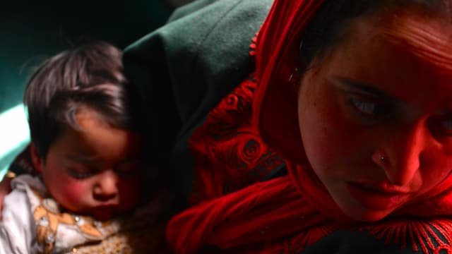 Die zweijährige Hiba schläft und schnarcht leise in den Armen ihrer Mutter.