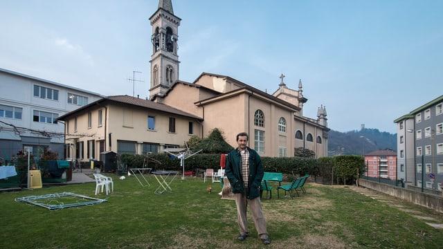Mann auf einem Rasenplatz vor einer Kirche.