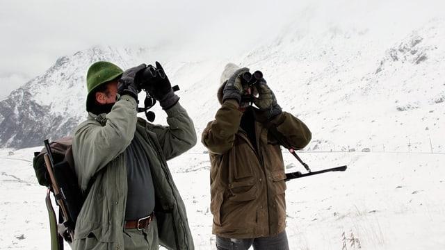 Zwei Jäger suchen die verschneite Gebirgslandschaft nach Wild ab.