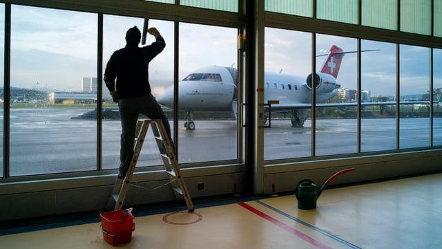 Ein Mann putzt die Scheiben des Rega-Hangars in Kloten, dahinter, draussen, ein Rega-Jet.