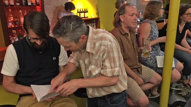 Männer und Frauen an einer Bar schauen Richtung Bühne. Zwei Männer blättern in einem Heft.