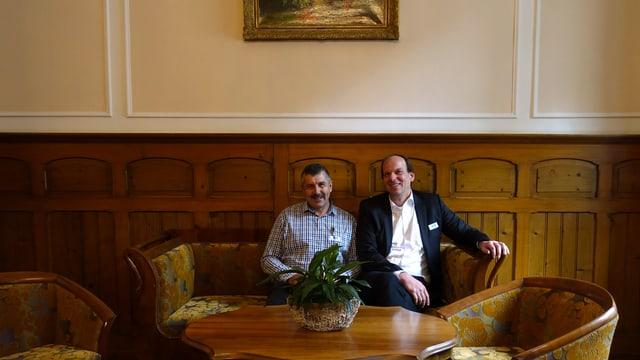 Zwei Männer sitzen auf einem Sofa.