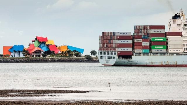 Das bunte Museum im Hintergrund, davor die Wasserstrasse, auf der ein Containerschiff fährt.