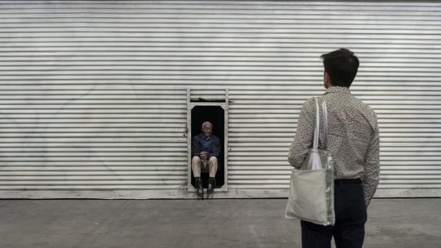 Man steht vor Mann, der in einem Türrahmen sitzt.