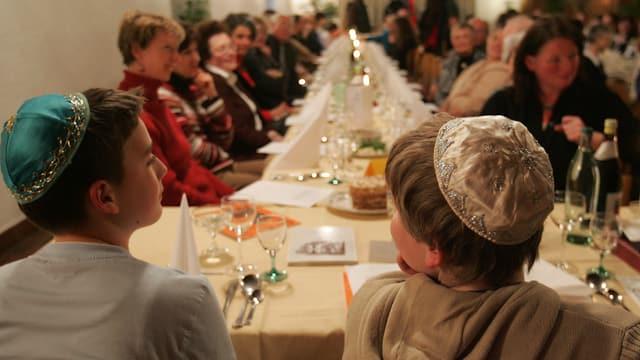 Gidieus durant ina festa tradiziunala enturn ina gronda maisa. Dus mats portan ina kippa.