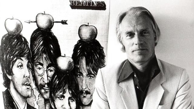 Ein Mann mit kinnlangem, weissem Haar steht vor einer Illustration der Beatles.