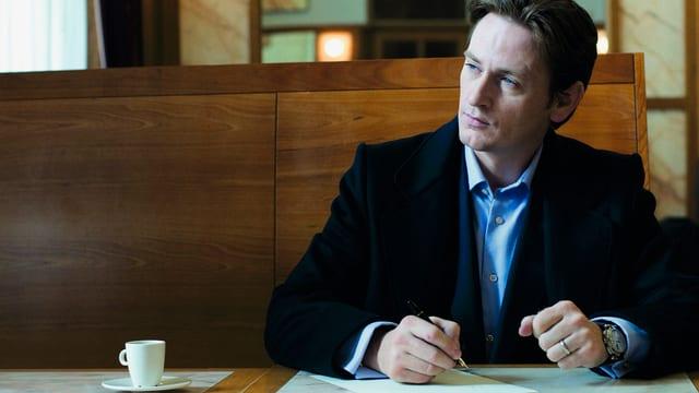 Ein Mann sitzt in einem Cafe und schreibt Notizen.