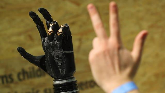 Eine Menschenhand zeigt einer Roboterhand, drei Finger in die Höhe zu strecken.