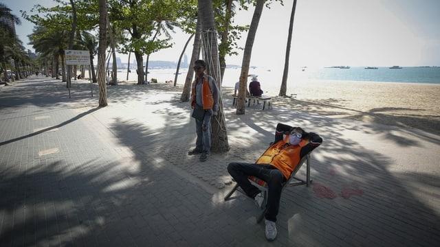 Mann mit Gesichtsmaske in einem Liegestuhl, dahinter ein leerer Strand.