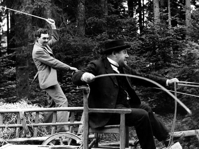 Zwei Männer auf Kutschen liefern sich ein Wettrennen. Der eine steht und holt mit der Peitsche aus.