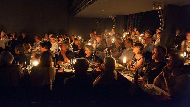 Viele Menschen sitzen in einem Saal an vielen kleinen Tischen und essen